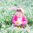 Girl playing with Easter eggs in a white basket sitting in a sunny garden — Stock Photo #43250517