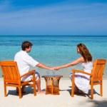 Couple enjoying cocktails on a tropical beach — Stock Photo