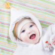 Cute funny laughing baby girl relaxing on a colorful blanket — Stock Photo
