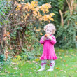 Toddler girl eating an apple in a garden — Stock Photo #43250619