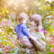 Woman playing with a happy baby girl in a garden — Stock Photo #43250663