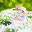Girl wearing bunny ears playing with Easter eggs — Stock Photo #43250749