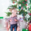 Toddler girl and baby brother under Christmas tree — Stock Photo