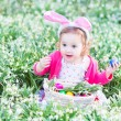 Girl playing with Easter eggs in a white basket sitting in a sunny garden — Stock Photo #43251929