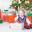 Toddler girl helping to decorate a Christmas tree — Stock Photo