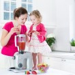 Irl and her young mother making fresh strawberry juice — Stock Photo #43252189