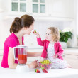 Irl and her young mother making fresh strawberry juice — Stock Photo #43252195