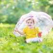 Baby girl under a colorful umbrella — Stock Photo #43252259