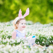 Girl wearing bunny ears playing with Easter eggs — Stock Photo #43252371