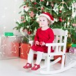 Toddler girl in a red dress and Santa hat — Stock Photo #43252443