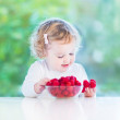 Little girl eating raspberry — Stock Photo #43252559