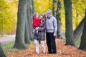 Family with a toddler girl walking together in a autumn park — Stock Photo