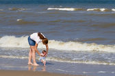 Mother and her newborn daughter on a beach — Stock Photo