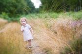 Baby girl walking in high grass — Stock Photo