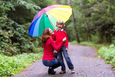 Mother and her son under a colorful umbrella — Stock Photo