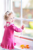 Toddler girl watching out of the window — Stockfoto
