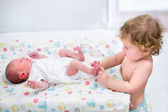 Toddler girl playing with the feet of her newborn baby brother — Stock Photo