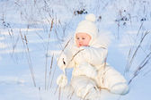 Funny baby playing with grass in a snow field — Stock Photo