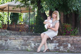 Elegant lady in a formal dress holding a baby — Stock Photo