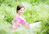 Pregnant woman relaxing in the garden — Stock Photo