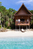 Man watching the ocean from a tropical bungalow — Stock Photo