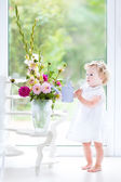 Toddler girl in a white dress watering flowers — Stock Photo