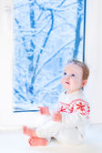 Beautiful baby girl sitting next to a window — Stock fotografie