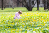 Baby girl playing with yellow flowers — Stock Photo
