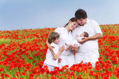 Family with two children in a red flower field — Stok fotoğraf