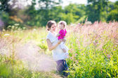 Mother holding her tired baby daughter in a park — Stock Photo