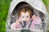 Baby girl sitting in a stroller — Stock Photo