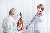 Great grandfarther listening to a child playing violin — Stock Photo