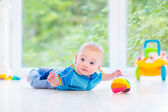 Adorable baby boy playing with a colorful ball and toy car — Stock Photo