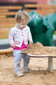 Baby girl playing with sand — Stockfoto