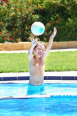 Boy playing with a ball in a swimming pool — Stock Photo