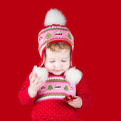 Baby girl playing with a red Christmas bow — Stock Photo