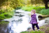 Baby girl playing at a river shore — Stockfoto