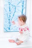 Beautiful baby girl sitting next to a window — Foto Stock