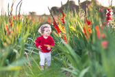 Curly baby girl walking on a farm — Stock Photo