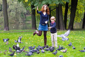 Mother and son feeding pigeons — Stock Photo