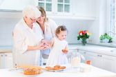 Woman baking a cake with her senior mother and cute toddler girl — Stock Photo