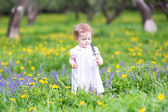 Beautiful little girl playing with flowers — Stock Photo