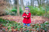 Toddler girl playing with snowdrop flowers — Stockfoto