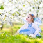 menina criança encaracolado em fantasia de fada tocando no jardim de frutas — Fotografia Stock  #46973995