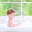 Funny baby girl playing with water and foam in a big kitchen sin — Stock Photo #46976201