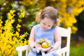 Cute curly toddler girl enjoying easter egg hunt in the garden — Stock Photo