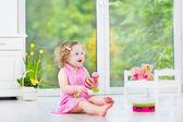 Cute curly toddler girl playing tambourine in a sunny white room — Stock Photo