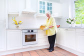 Happy grandmother baking a pie in a white kitchen — Stock Photo