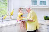 Glückliche großmutter und kleines mädchen backen einen kuchen in einem weißen v — Stockfoto