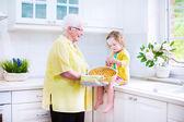 Gelukkig grootmoeder en meisje bakken van een taart in een witte garage — Stockfoto